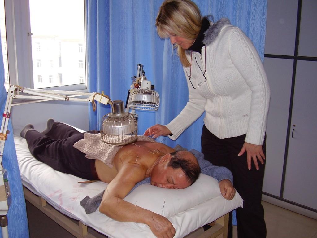 Bild på Tuula som utför akupunktur på en liggande patient.